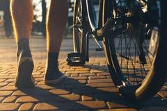 Beine eines Mannes in den Turnschuhen und in einem Stadtfahrrad bewegen sich über die Kopfsteine vor dem hintergrund des hellen S Lizenzfreies Stockfoto