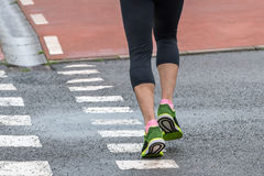 Beine eines Mannes, der auf der Straße läuft Stockfotografie