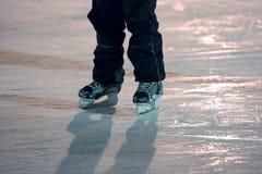 Beine eines Mannes, der auf die Eisbahn eisläuft Stockfotografie