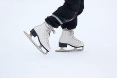 Beine eines Mannes, der auf eine Eisbahn eisläuft Stockfotos