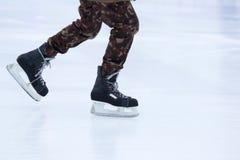 Beine eines Mannes, der auf eine Eisbahn eisläuft Lizenzfreies Stockbild