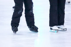 Beine eines Mannes, der auf eine Eisbahn eisläuft Stockbild