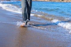 Beine eines Mannes, der entlang den Strand geht Stockfoto