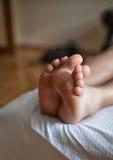 Beine eines Mannes, der im Bett schläft Lizenzfreie Stockfotos
