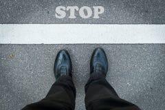 Beine eines Mannes mit Stoppschild Lizenzfreie Stockbilder