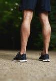 Beine eines muskulösen athletischen Mannes des Sitzes Lizenzfreie Stockfotos
