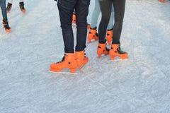 Beine in eislaufenden orange Schuhen stockfotografie