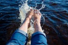 Beine im Wasser heben Wasser mit einem Spray an Stockfoto