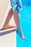 Beine mit Fußgefühls-Wassertemperatur im Swimmingpool Stockbild