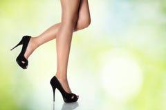 Beine mit schwarzen Stöckelschuhen auf einem grünen Hintergrund Lizenzfreie Stockfotos