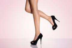 Beine mit schwarzen Stöckelschuhen auf einem rosa Hintergrund Stockfotografie