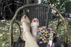 Beine mit Tasche auf dem Stuhl Stockfotos