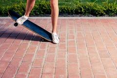 Beine og sportliches Mädchen, das einen Trick auf einem Skateboard tut stockfoto