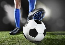 Beine und Füße des Fußballspielers in den blauen Socken und schwarzen in den Schuhen, die mit dem Ball spielt auf grünem Gras auf Stockfotos