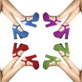 Beine und Füße einer Frau mit farbigen Schuhen im Kreis Lizenzfreie Stockbilder