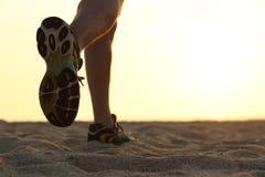 Beine und Schuhe eines Mannes, der bei Sonnenuntergang läuft Lizenzfreie Stockfotografie