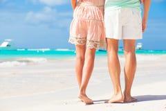 Beine von den Jungen, die Paare auf tropischem Türkisstrand umarmen Stockfoto
