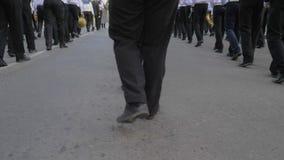 Beine von den jungen Seeleuten, die in der Hand mit Musikinstrumenten auf Parade in der Straße marschieren stock footage