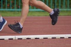 Beine von den Männern, die in die Laufbahn laufen stockfoto