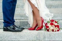 Beine von Hochzeitspaaren und -blumenstrauß Lizenzfreie Stockbilder