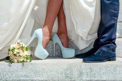 Beine von Hochzeitspaaren und -blumenstrauß Lizenzfreies Stockfoto