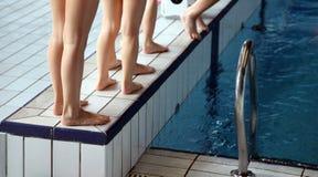 Beine von Kindern während des Swimmingpools Stockfotos