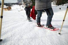 Beine von Leuten beim Snowshoeing in den Bergen Stockfotografie