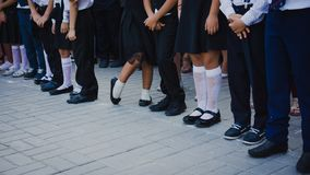 Beine von M?dchen im wei?en Golf und von Jungen in den Anzugshosen stehen in der Linie in der Schule Bahn am 1. September 1. Sept lizenzfreie stockbilder