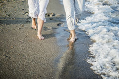 Beine von Paaren auf dem Sandstrand Stockbild