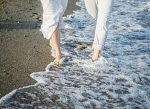 Beine von Paaren auf dem Sandstrand Lizenzfreie Stockfotografie