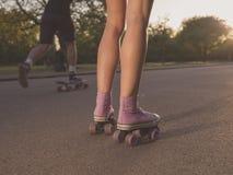 Beine von Rollschuhlaufen der jungen Frau im Park Lizenzfreie Stockfotos