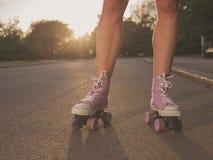 Beine von Rollschuhlaufen der jungen Frau im Park Lizenzfreie Stockfotografie