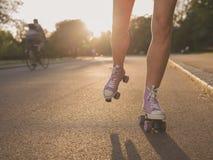 Beine von Rollschuhlaufen der jungen Frau im Park Stockfotografie