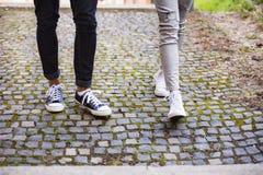 Beine von zwei unerkennbaren jungen Touristen in der alten Stadt Lizenzfreie Stockfotografie