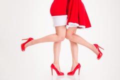 Beine in Weihnachtsmann-Kostümen und in den roten Schuhen der hohen Absätze Lizenzfreies Stockfoto