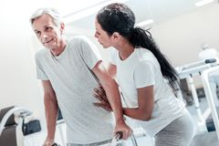 Inspired old man exercising and a woman helping him. Being active. Joyful concentrated old grey-haired men exercising while a pretty dark-haired afro-american Royalty Free Stock Photography