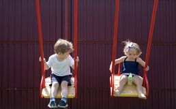 Being active outside. Small children with blond hair on swing. Girl and boy haircut styles. Hair salon for children. Small brother and sister enjoy playing royalty free stock images