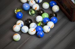 Being a child is playing a marble. The colors are colored marbles, beautiful-looking marbles Stock Photos