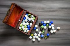 Being a child is playing a marble. The colors are colored marbles, beautiful-looking marbles Stock Photo