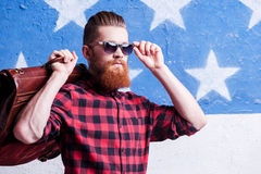 Being cool is simple thing. Handsome young bearded man adjusting his sunglasses and holding a suitcase on his shoulder while standing against American flag royalty free stock photos