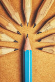Being different concept with wood pencils on desk. Contempt toward unique ones, being different, weird, surrounded by adversity, judging the odd one, wood Royalty Free Stock Image