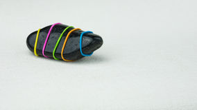 Being different one black stone with coloured stripes on bright background Stock Photography