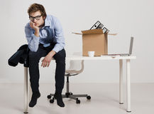 Being fired. Young man sitting on the desk after being fired Royalty Free Stock Images