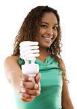 Being green. Stock image of girl holding an energy saving compact flourescent light bulb over white background, selective focus on hand and light bulb Stock Photo