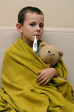 Being ill. Young child with thermometer and sweet teddy bear with flu and fever. Child with a temperature Stock Photo