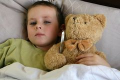 Being ill. Young child with thermometer and sweet teddy bear lying in bed with flu and fever. Child with a temperature Stock Images