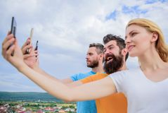 Being narcissistic. People enjoy selfie shooting on natural landscape. woman and men holding smartphones in hands. Being narcissistic. People enjoy selfie royalty free stock photo