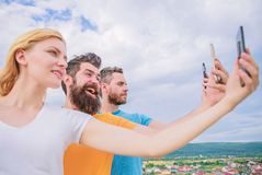 Being narcissistic. People enjoy selfie shooting on natural landscape. Sexy woman and men holding smartphones in hands royalty free stock image