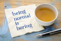 Being normal is boring - napkin concept. Being normal is boring  - handwriting on a napkin with a cup of tea Stock Image