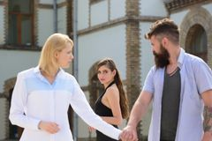 Being odd woman out. Love triangle and threesome. Bearded man looking at other girl. Hipster choosing between two women. Being odd women out. Love triangle and stock image